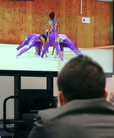 大会本部のモニターに映された、演技する水俣ジュニアクの中継映像=東京都内