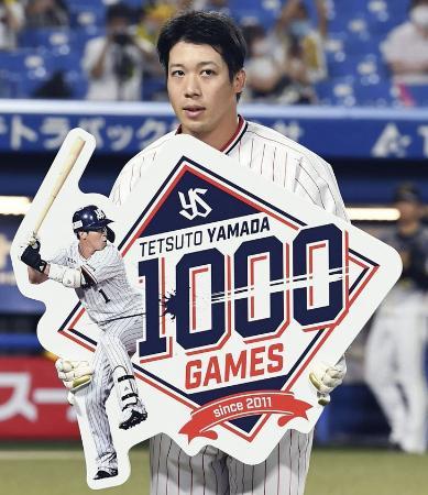 通算千試合出場を達成し、記念のボードを手にするヤクルト・山田哲=神宮