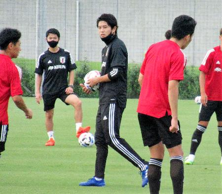 サッカーU―19日本代表候補合宿で練習を見守る元日本代表DF内田篤人氏(中央)=14日午後、千葉県内
