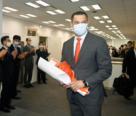 スポーツ庁に初登庁し、花束を受け取った室伏広治長官=1日午前、東京都千代田区
