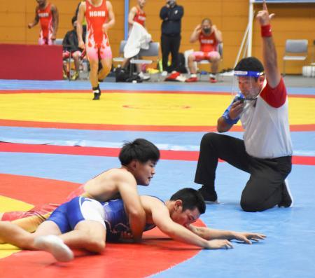 レスリングの全国高校選抜大会でプレーする選手と、フェースシールドを着けた審判員=9日、新潟市東総合スポーツセンター