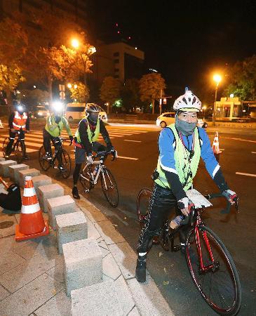 東京五輪のマラソンコースの計測をする日本陸連と世界陸連の関係者ら=10日未明、札幌市(代表撮影)