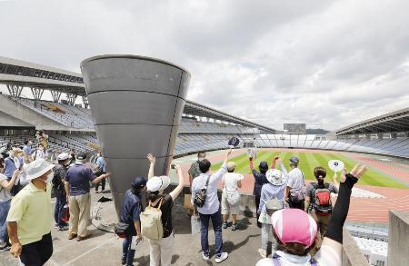 五輪ボランティアを対象にサッカー会場となる宮城スタジアムで行われた見学会で、大型スクリーンに向かって手を振る参加者=7月、宮城県利府町
