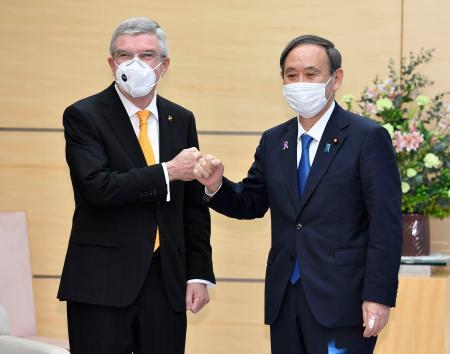 会談を前にIOCのバッハ会長(左)とグータッチを交わす菅首相=16日午前、首相官邸