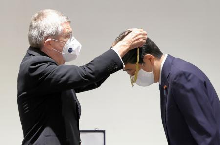 IOCのバッハ会長(左)から五輪運動の発展に寄与したことをたたえる「五輪オーダー」を授与される安倍前首相=16日午後、東京都新宿区の日本オリンピックミュージアム(代表撮影)