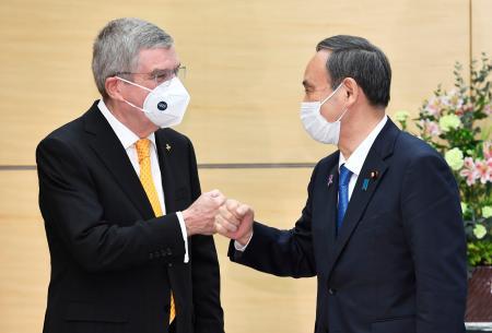 会談を前にIOCのバッハ会長(左)とグータッチを交わす菅首相。東京五輪・パラリンピックを必ず実現するとの方針で一致した=16日、首相官邸