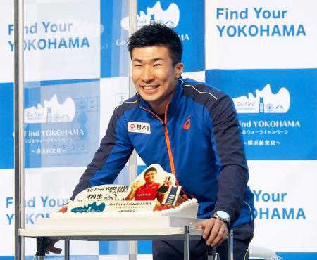 イベントで誕生日ケーキを贈られ、笑顔を見せる陸上男子短距離の桐生祥秀=11日、横浜市