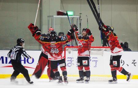 アイスホッケーの全日本選手権で優勝し、氷上で喜ぶひがし北海道の選手=テクノルアイスパーク八戸