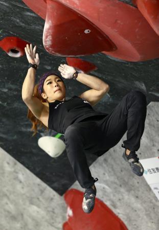 女子決勝 ボルダリング第3課題でホールドに飛びつく野中生萌=石鎚クライミングパークSAIJO