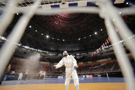世界ハンドボール会場で、試合後に防護服姿で消毒を行う作業員=16日、カイロ(ロイター=共同)