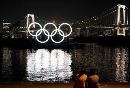 東京・お台場の水上に浮かぶ五輪マークのモニュメント。彼女と並んでじっと眺めていた三浦佑太さん(29)は「初めて来たが、東京を象徴する場所だなと思った。東京五輪は無事に開催されればいいな」と語った=22日夕