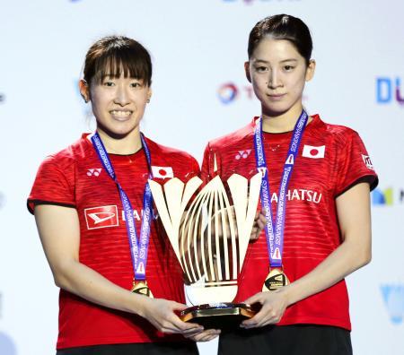 バドミントンのスーパーシリーズ女子ダブルスで初優勝し、表彰式でトロフィーを手にする米元小春(右)、田中志穂組=2017年12月、ドバイ(AP=共同)
