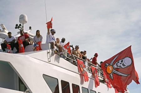 ボートでの優勝パレードで、ファンに手を振るバッカニアーズの選手ら=10日、タンパ(AP=共同)
