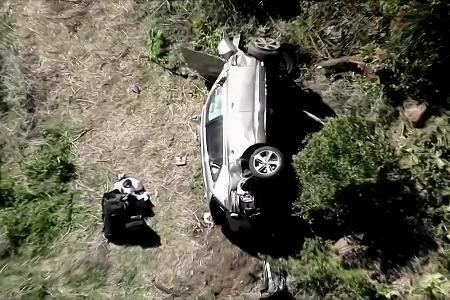 道路脇に横転したタイガー・ウッズ選手運転の乗用車=23日、ロサンゼルス(KNBC提供・ロイター=共同)