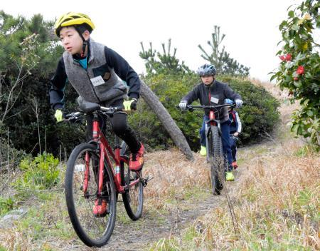 「キッズトライアスロン教室」で、起伏のある松林を自転車で走る小学生=13日午後、鳥取県米子市