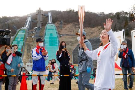 白馬ジャンプ競技場に到着し、笑顔で走る聖火ランナーの上村愛子さん=1日午後、長野県白馬村