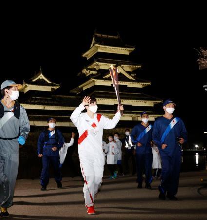 トーチを掲げて走る聖火ランナーの小平奈緒さん。奥は松本城=2日夜、長野県松本市
