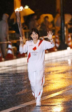 大粒の雨の中、沿道の人たちに笑顔で手を振る聖火ランナーの高橋尚子さん=4日夜、岐阜市