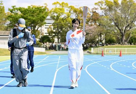 愛知県豊橋市で陸上競技場のトラックを走る聖火ランナーの松井玲奈さん=6日午前