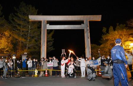伊勢神宮内宮の鳥居前で聖火を引き継ぐランナー=7日夜、三重県伊勢市