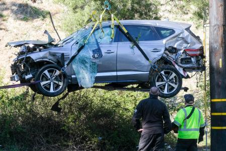 クレーンで引き上げられるタイガー・ウッズ選手の事故車両=2月23日、米ロサンゼルス近郊(AP=共同)