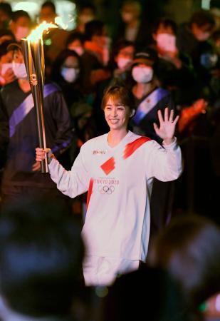 聖火のトーチを掲げて走る田中理恵さん=9日夜、和歌山市