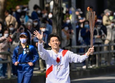 聖火のトーチを掲げて走る田中和仁さん=10日午前、和歌山市