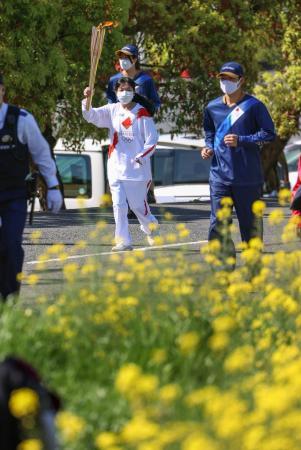 菜の花が咲く奈良県五條市のコースを、聖火のトーチを掲げて走るランナー=11日午前