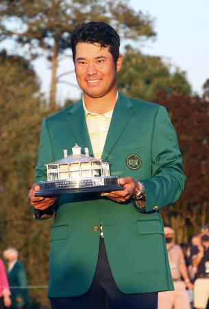 米ゴルフのマスターズ・トーナメントで、日本男子初のメジャー制覇を果たし、トロフィーを手に笑顔の松山英樹=11日、米ジョージア州のオーガスタ・ナショナルGC(共同)