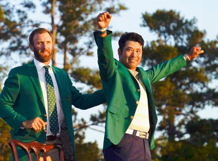 米ゴルフのマスターズ・トーナメントで日本男子初のメジャー制覇を果たし、グリーンジャケットを着て喜ぶ松山英樹。左は前年優勝のダスティン・ジョンソン=11日、米ジョージア州のオーガスタ・ナショナルGC(AP=共同)