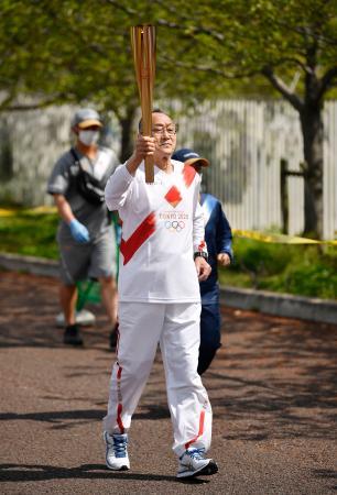 聖火のトーチを掲げて走る西村成生さん=14日午前、大阪府吹田市の万博記念公園
