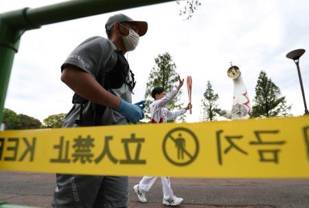 大阪府吹田市の万博記念公園で、太陽の塔の前を走る聖火ランナー。同府での聖火リレーは、新型コロナウイルス感染拡大で公道の走行を中止し、公園内のコースを周回する異例の形で行われた=14日午後
