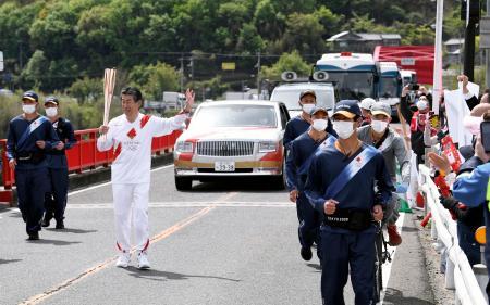 吉野川に架かる「美馬橋」付近を通過する聖火ランナー=15日午前、徳島県美馬市