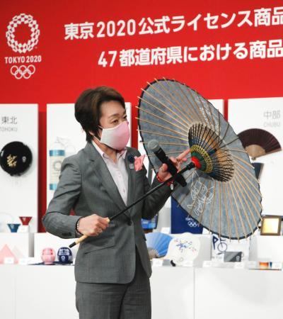 大会公式商品の加賀友禅マスクを着け、伝統工芸品を紹介する東京五輪・パラリンピック組織委の橋本聖子会長=15日午後、東京都中央区