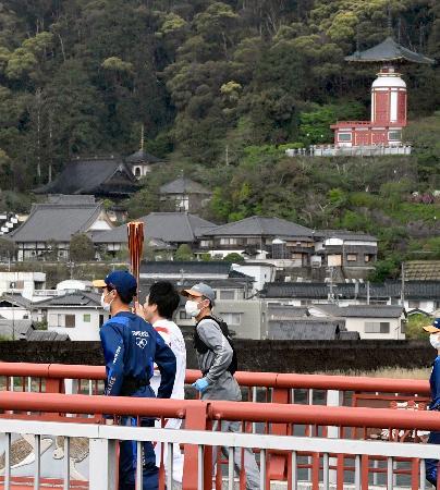 徳島県美波町で聖火のトーチを掲げ走るランナー。奥は四国八十八カ所霊場の一つ薬王寺=16日午前