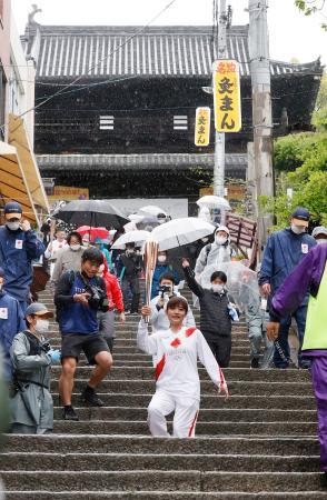 香川県琴平町の金刀比羅宮大門(奥)前の石段で、トーチを掲げ聖火を運ぶランナー=17日午後