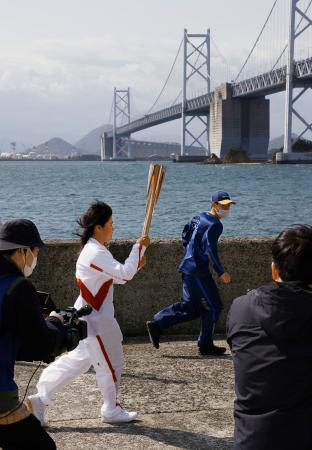 聖火のトーチを掲げて瀬戸大橋(奥)の近くを走る岩中楓さん=18日午前、香川県坂出市の与島