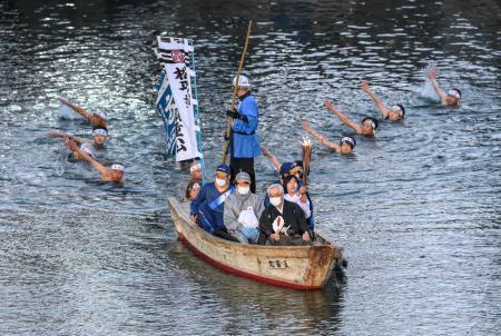 高松城跡の堀で和船に乗り込みトーチを掲げ聖火を運ぶ田野口佳奈さん。後方から約10人が泳いで続いた=18日夕、高松市