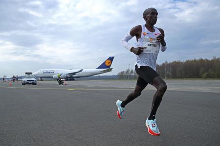 NNミッション・マラソンで空港内の周回コースを航空機をバックに走るエリウド・キプチョゲ=18日、エンスヘーデ(ゲッティ=共同)