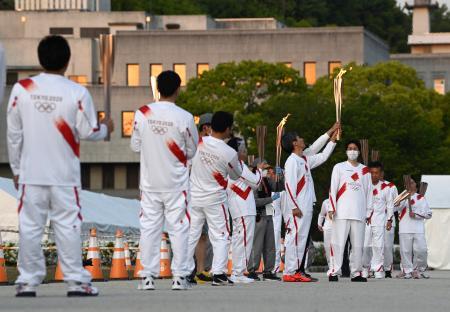 松山市では新型コロナウイルス感染拡大の影響で公道での聖火リレーが中止となり、市内の公園で「点火セレモニー」が開かれた。走る機会がなくなったランナーがトーチで聖火をつないだ=21日午後