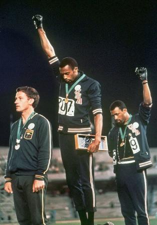 1968年メキシコ五輪の陸上男子200メートルで、表彰式で黒い手袋をはめ「無言の抗議」をする米国の2選手(AP=共同)