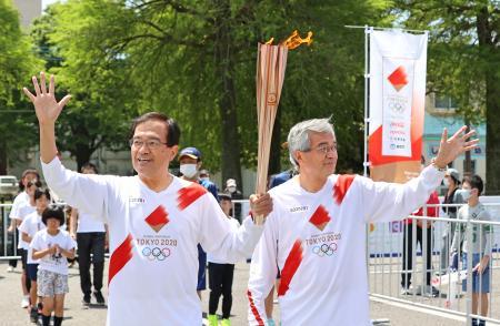 宮崎県延岡市を走る聖火ランナーの宗茂さん(左)、猛さん兄弟=25日午前(代表撮影)