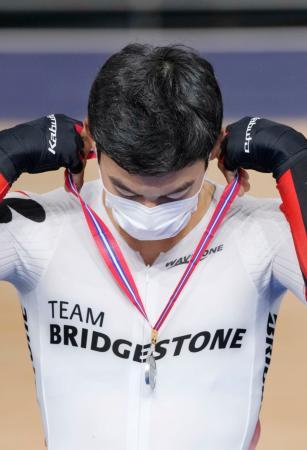 自転車トラック種目テスト大会の表彰式でメダルを自ら首に掛ける選手=25日、伊豆ベロドローム