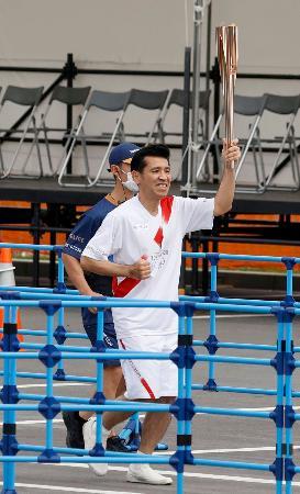 沖縄県名護市民会館周辺を走る聖火ランナーのゴリさん=1日午前