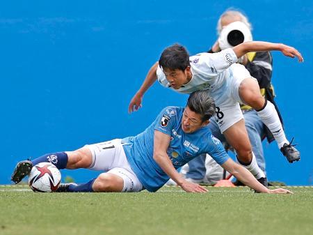 横浜FC―湘南 後半、激しく競り合う横浜FC・三浦(下)と湘南・平岡。大会最年長出場記録を更新した=ニッパツ