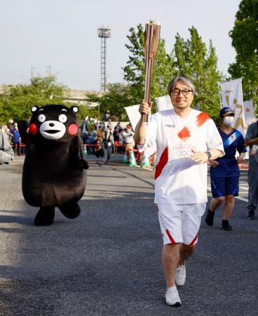 聖火ランナーを務めた小山薫堂さん。奥は応援に駆け付けたくまモン=5日午後、熊本県宇土市