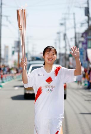 熊本県益城町でトーチを掲げて走る聖火ランナーの亀山ほのかさん=6日午前