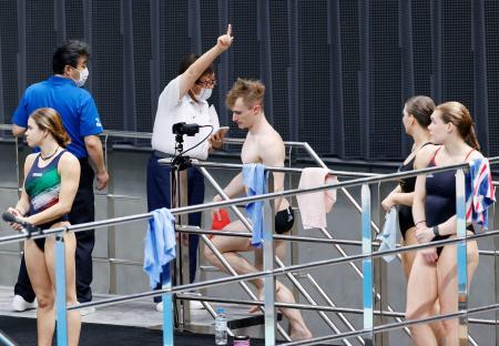 飛び込みのW杯で、練習する選手が密集しないよう誘導する係員=6日、東京アクアティクスセンター