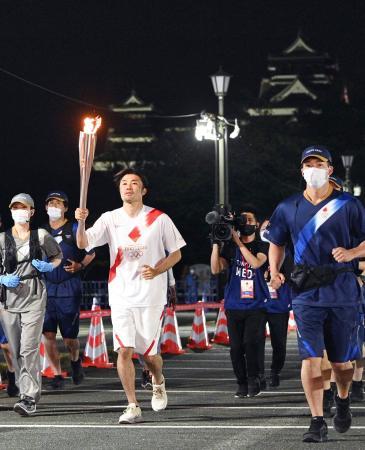 一般客の入場が制限された熊本城二の丸駐車場を走る聖火ランナーの末続慎吾さん=6日夜、熊本市