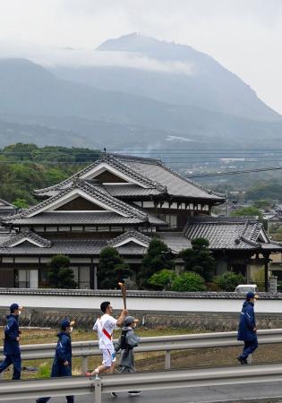 長崎県南島原市でトーチを掲げ走る聖火ランナー。奥は雲仙・普賢岳=7日午前